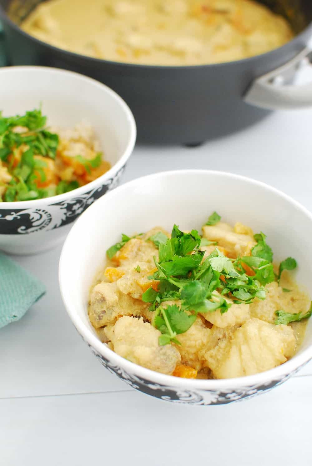A bowl full of thai fish curry garnished with cilantro