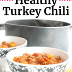 healthy turkey chili in a black and white bowl, next to a pot of chili