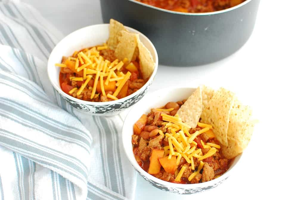 Two bowls of healthy turkey chili topped with cheddar and tortilla chips