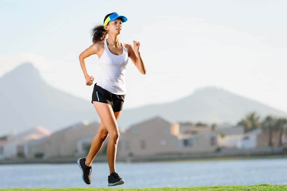 a woman running outside on grass