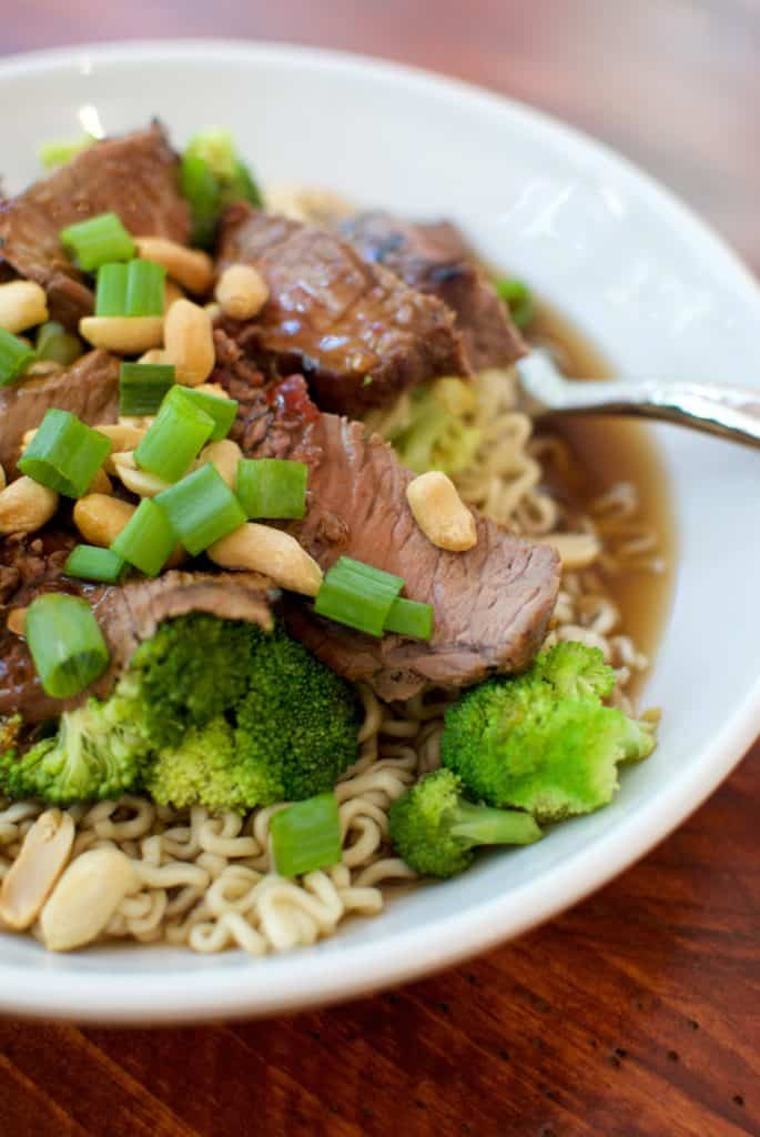 Beef and broccoli ramen in a white bowl topped with peanuts