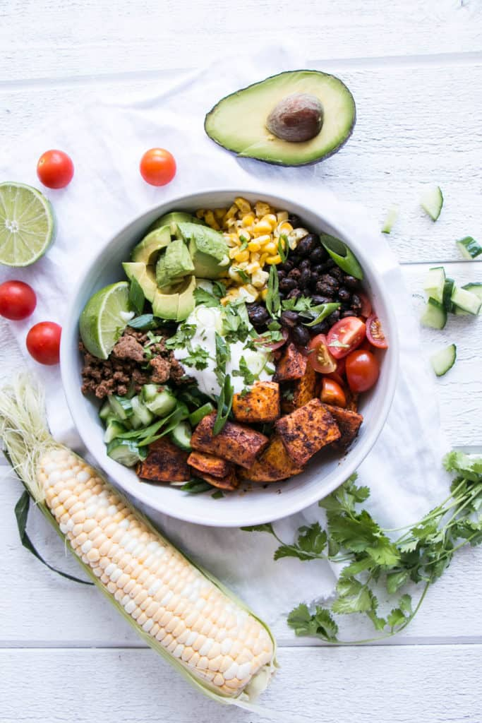 Sweet Potato Taco Bowl on a table beside avocado