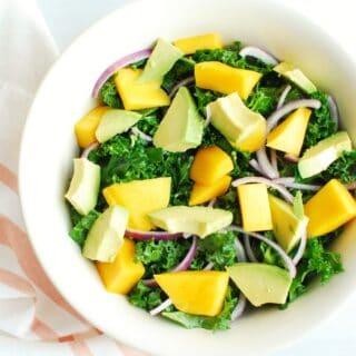 Kale mango salad in a large white bowl
