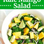 A bowl full of kale mango salad next to a napkin