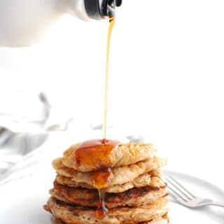 A stack of low calorie pancakes with maple syrup drizzled on top.