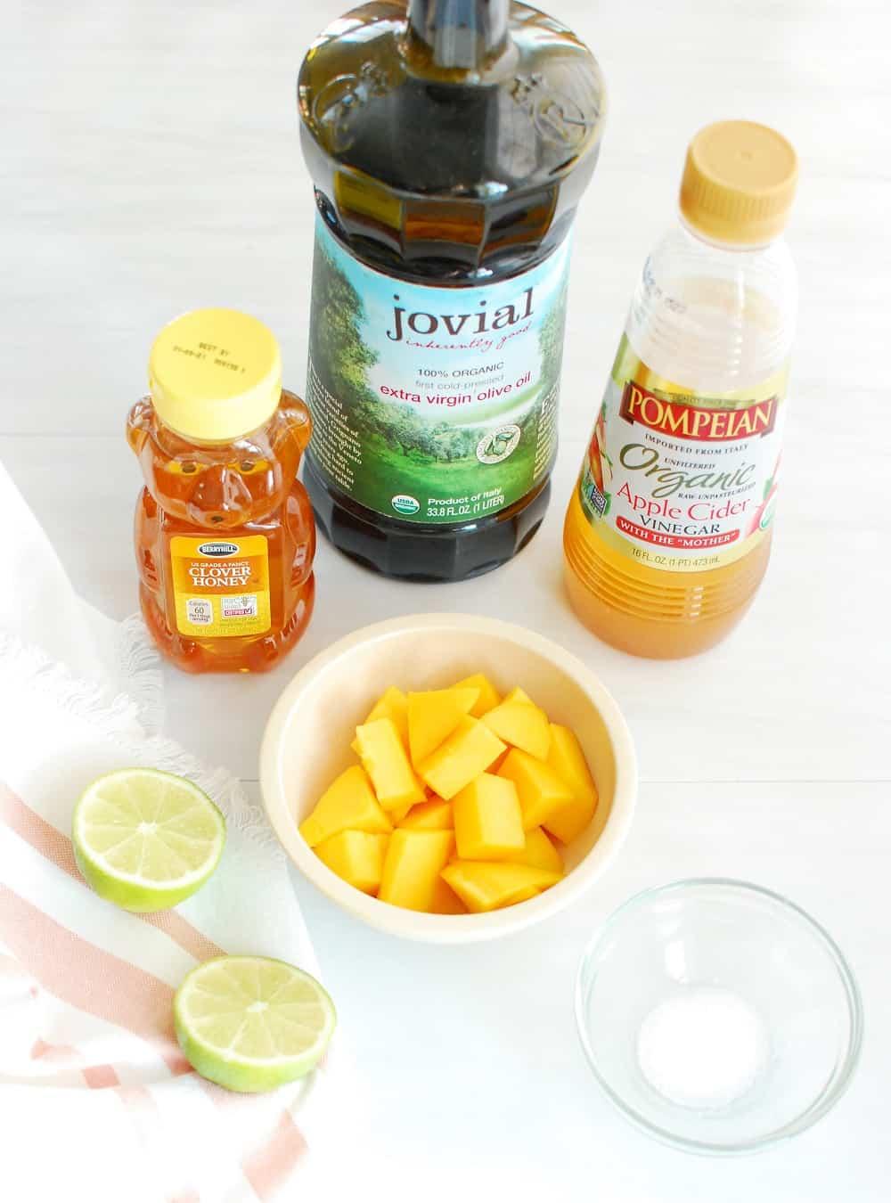 Ingredients to make a homemade salad dressing including mango, lime, honey, vinegar, oil, and salt