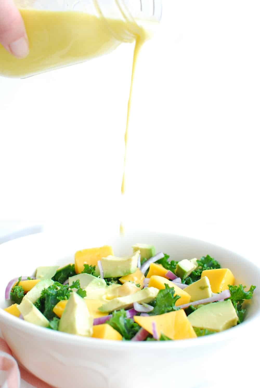 Someone drizzling mango dressing into a bowl of salad