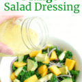 someone pouring mango salad dressing over a large bowl of kale salad
