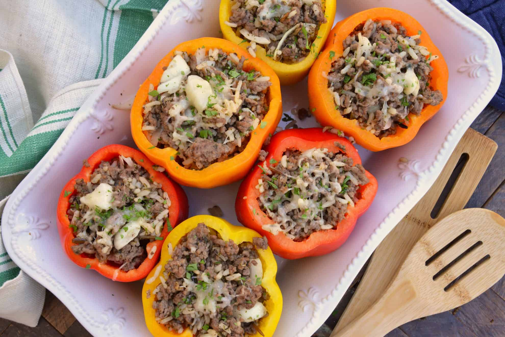 Stuffed Peppers in a white casserole dish beside a wooden spoon