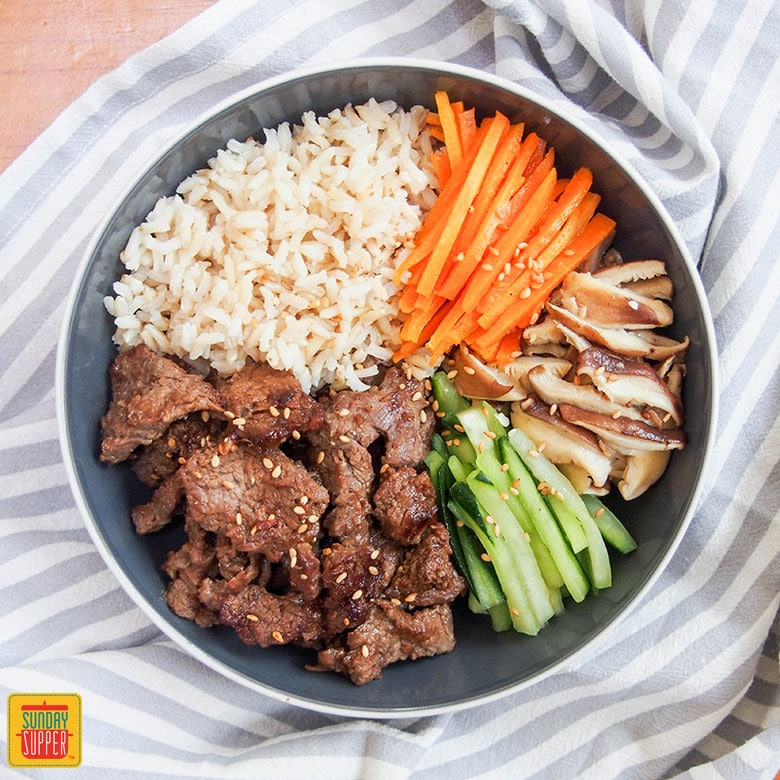 Beef bulgogi meal prep bowl and a stripped towel with rice and vegetables