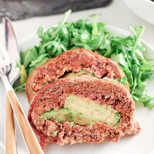Mexican meatloaf on a white plate beside a salad with utensils