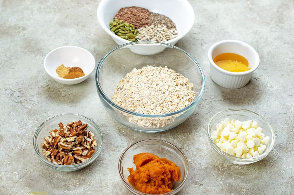 Ingredients for the recipe including oats, pumpkin, seeds, white chocolate, and honey