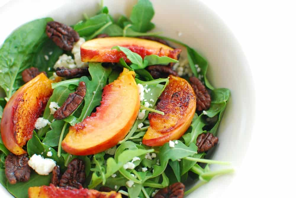 Close up of a spinach arugula salad with peaches, pecans, and blue cheese