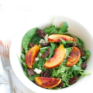 A white bowl full of arugula spinach salad with peaches, pecans, and blue cheese
