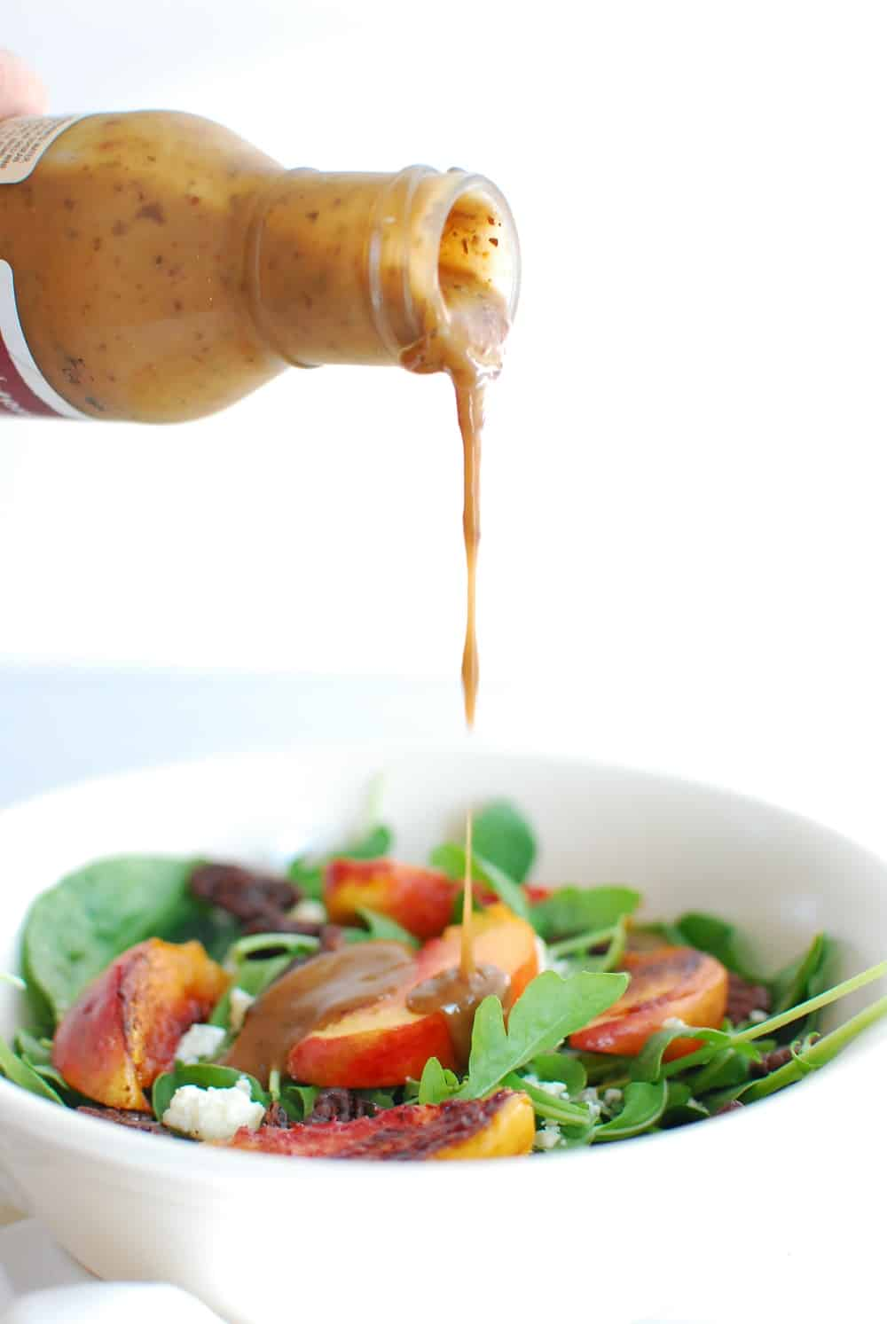 Balsamic dressing being drizzled on top of a spinach arugula salad