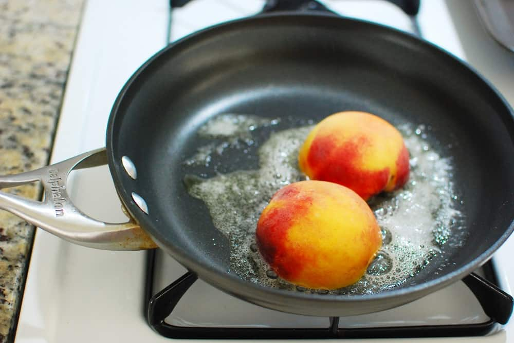 Cooking peaches in a skillet with butter