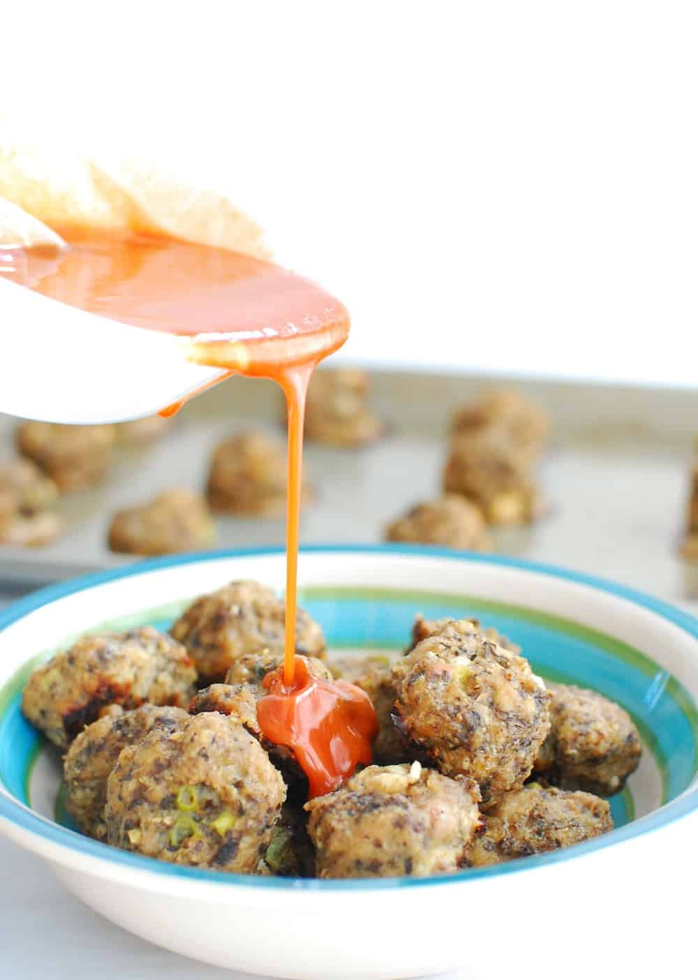Pouring buffalo sauce over turkey meatballs