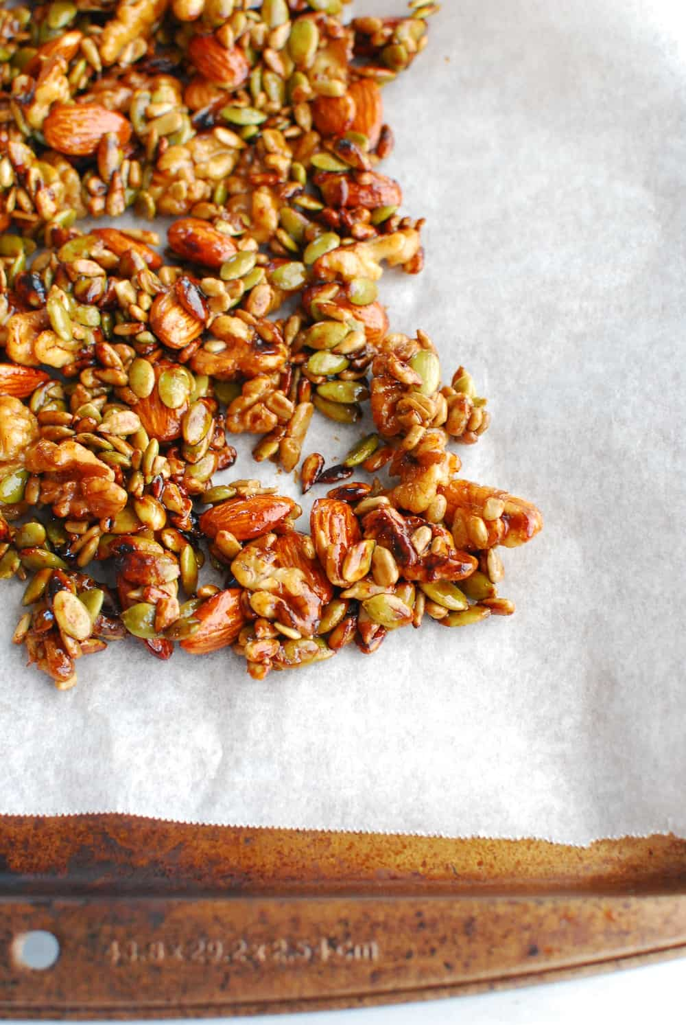 Maple glazed nuts and seeds drying on parchment paper