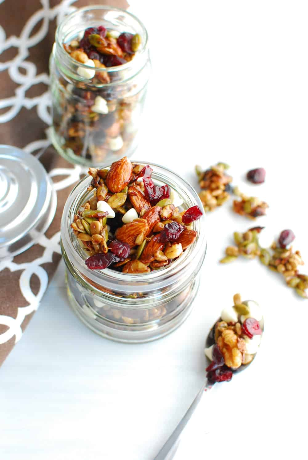Fall trail mix in a jar next to a spoon of spilled trail mix