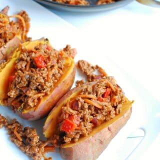 BBQ ground beef stuffed sweet potatoes on a white platter