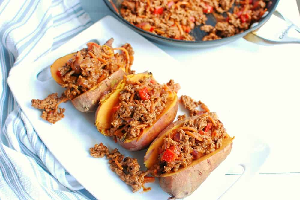 ground beef stuffed sweet potatoes on a white plate