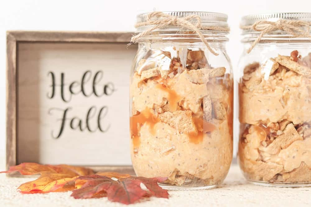 two mason jars of pumpkin overnight oats next to a sign that says hello fall