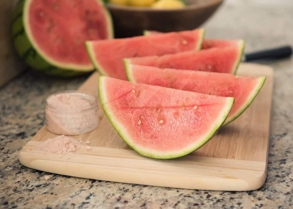 Several sliced pieces of watermelon on a cutting board