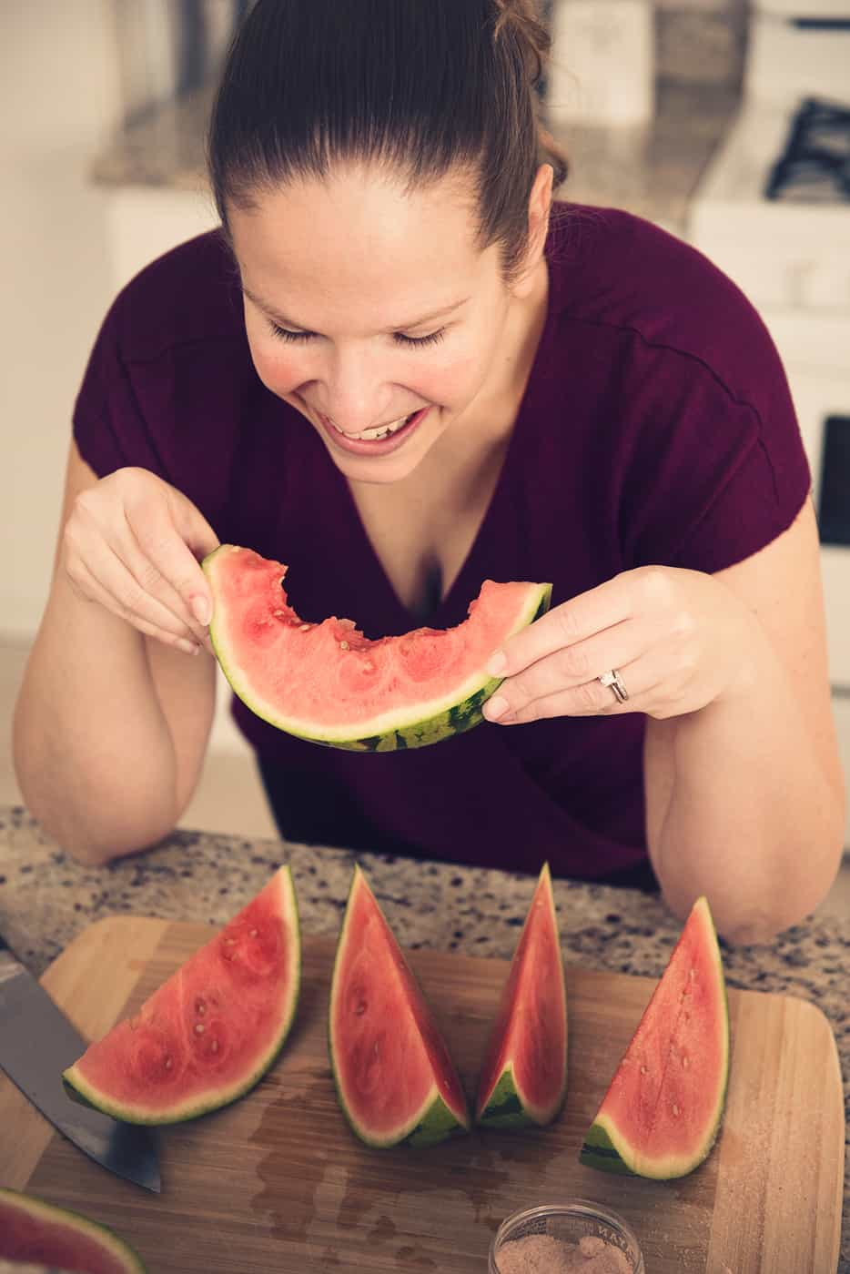 A woman eating a slice of watermelon at the kitchen counter
