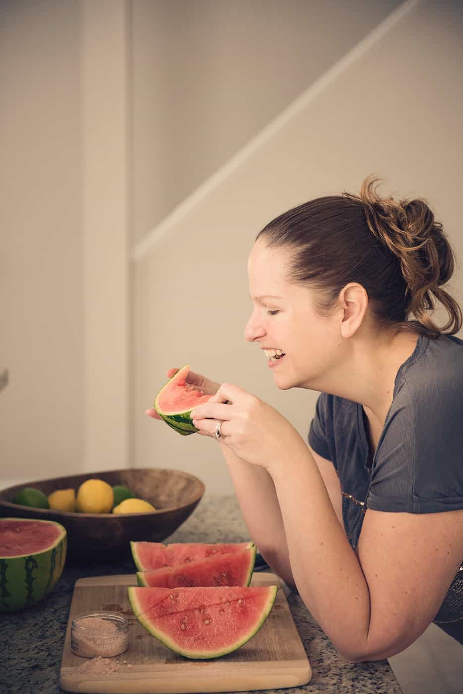 A woman enjoying a slice of watermelon without worrying about if its fattening