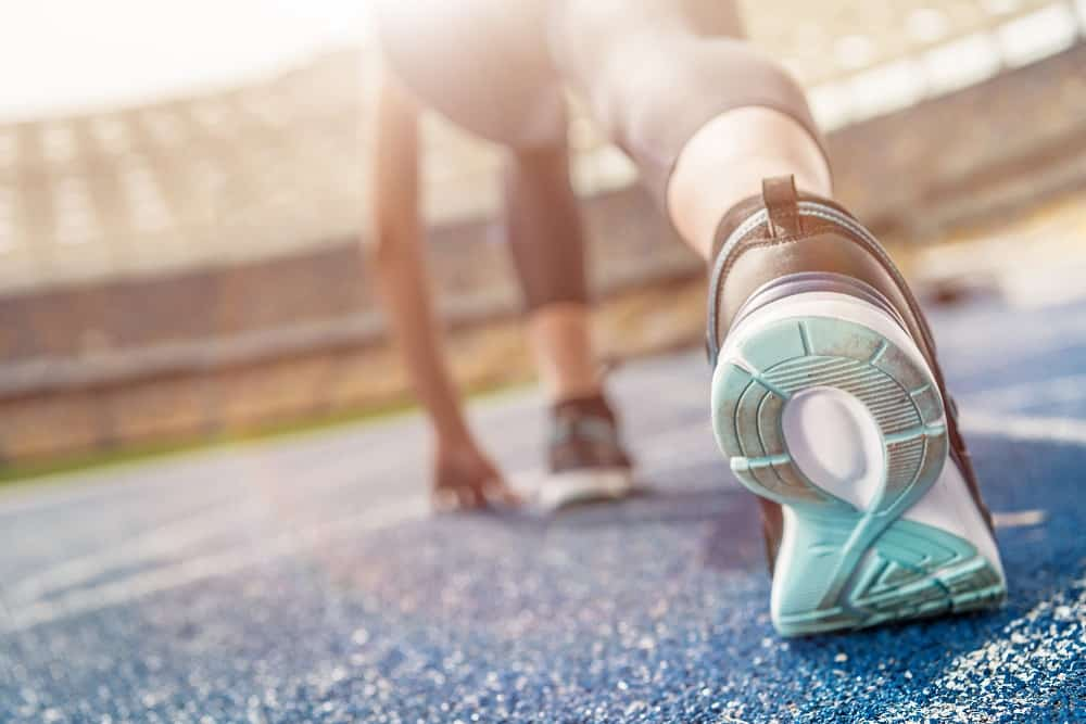 A close up of a woman's shoe as she gets ready to run 2 miles on a track