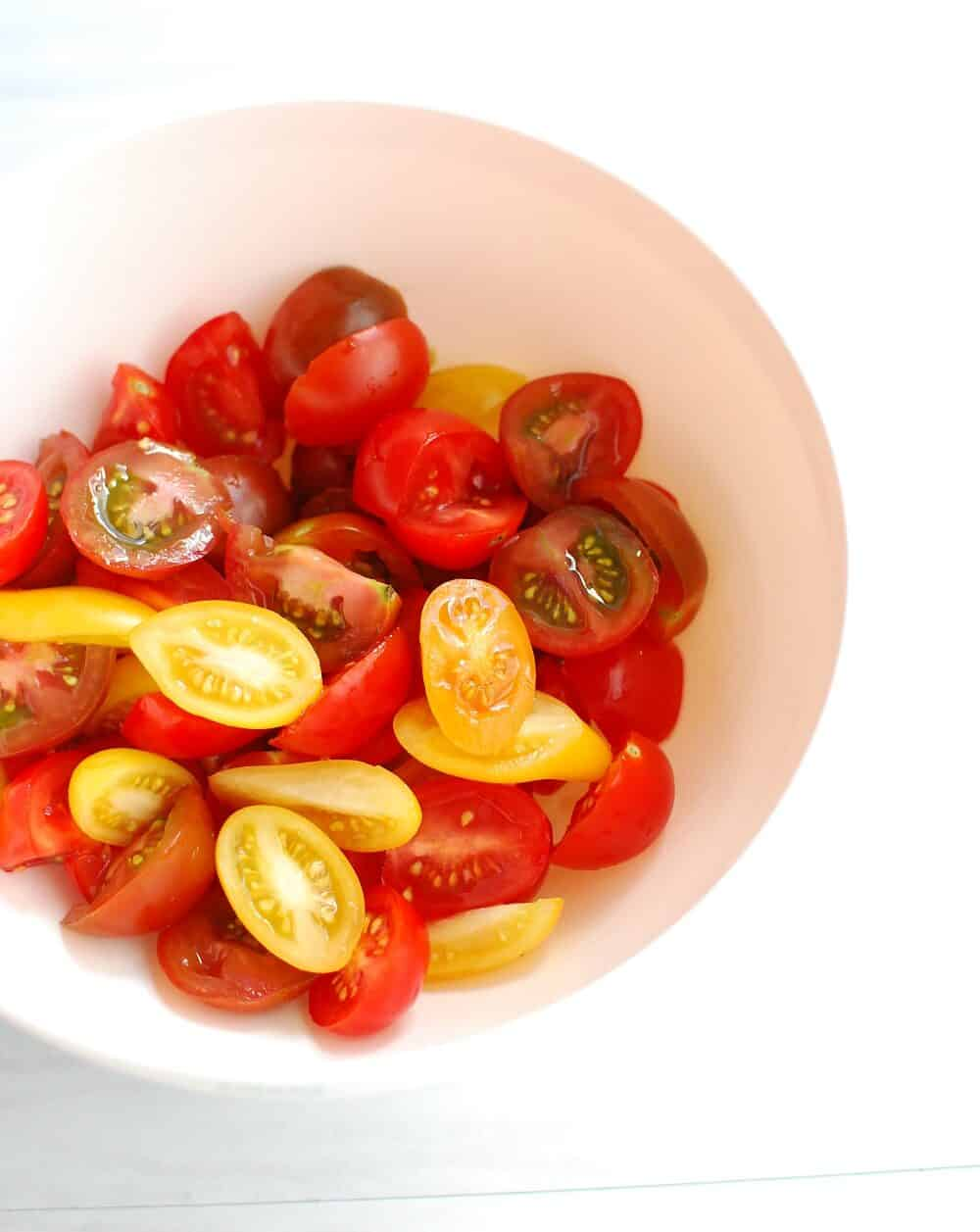 A bowl full of sliced cherry tomatoes
