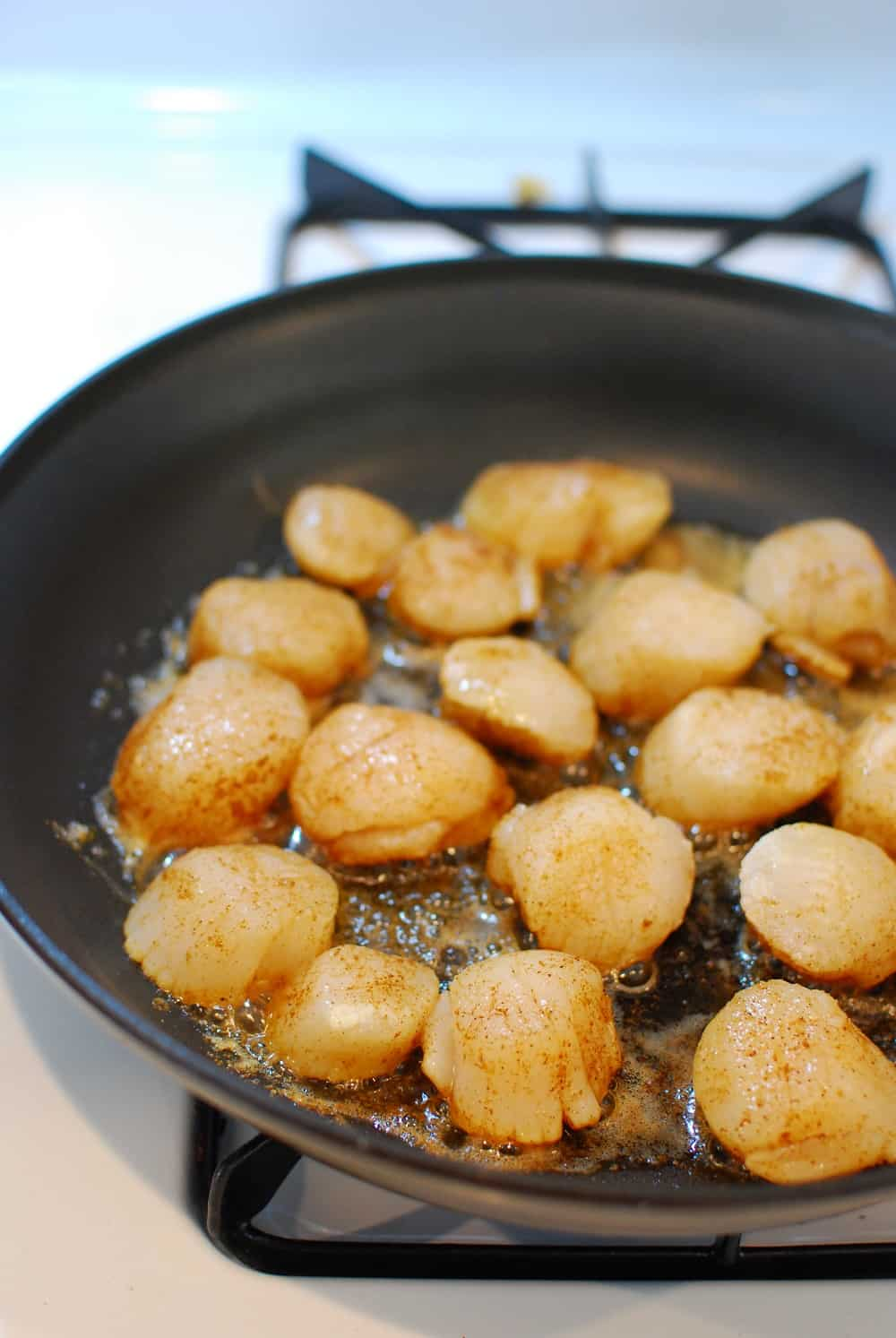 scallops cooking in a pan with butter
