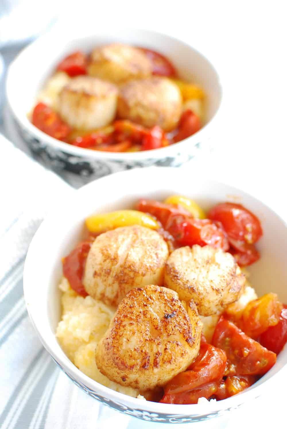 A bowl full of scallops and grits along with balsamic cherry tomatoes