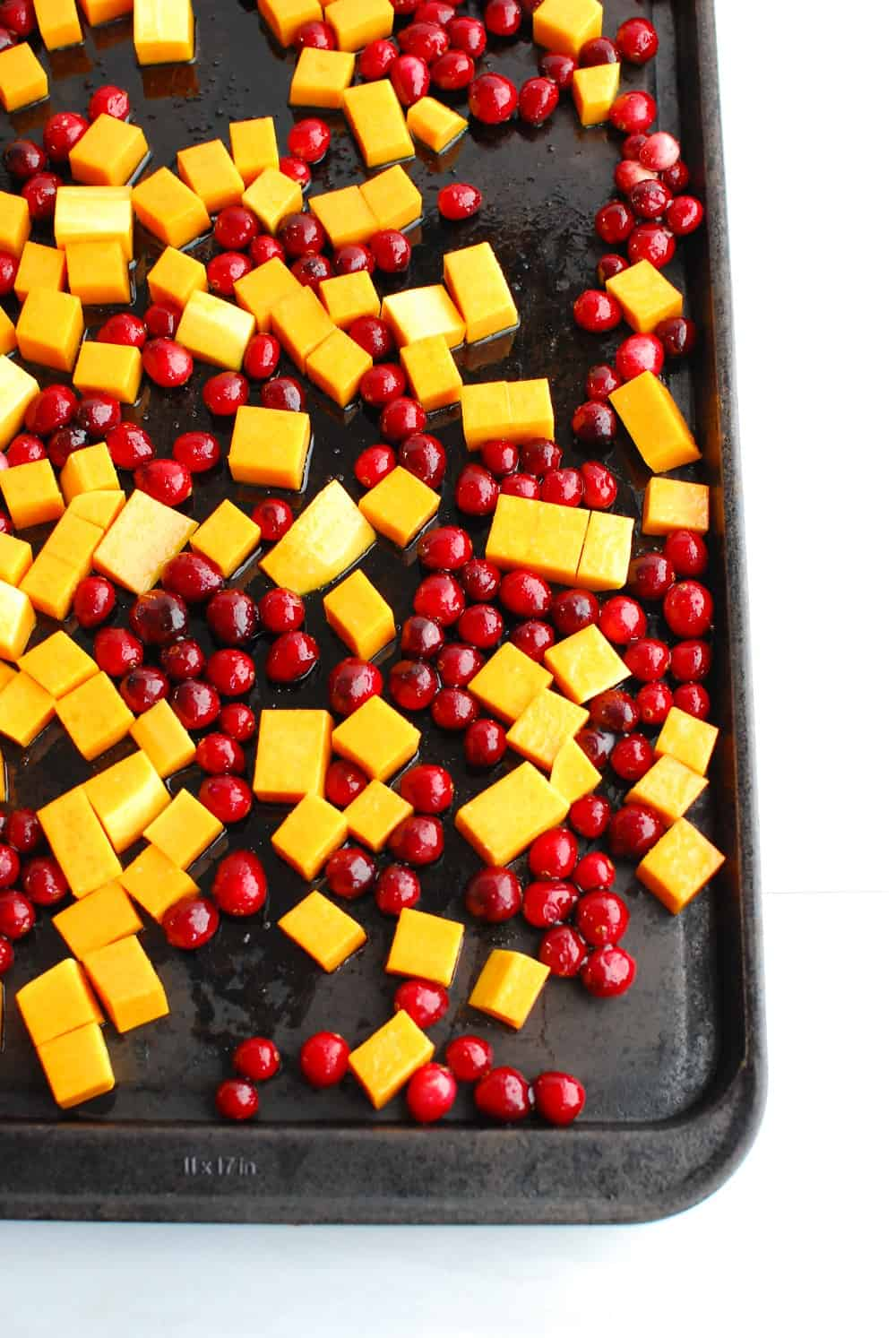 butternut squash and cranberries on a baking sheet prior to cooking