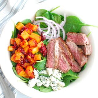 A steak and blue cheese salad with butternut squash and cranberries in a white bowl