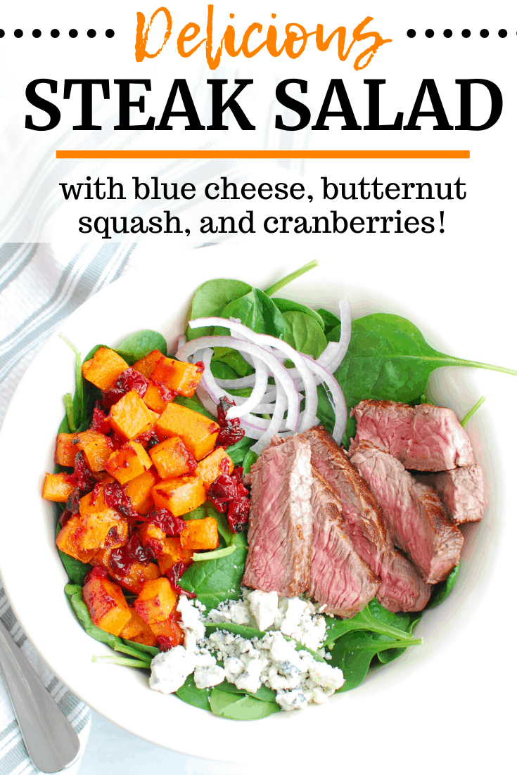 A steak salad with blue cheese, butternuts squash, cranberries, and spinach in a white bowl