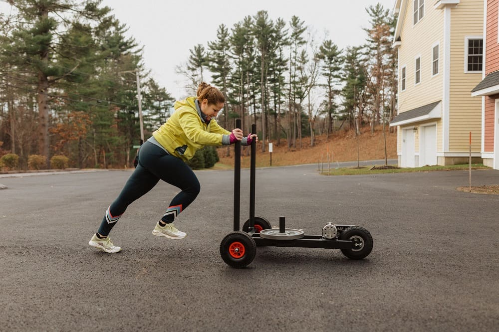 a woman using a weight sled