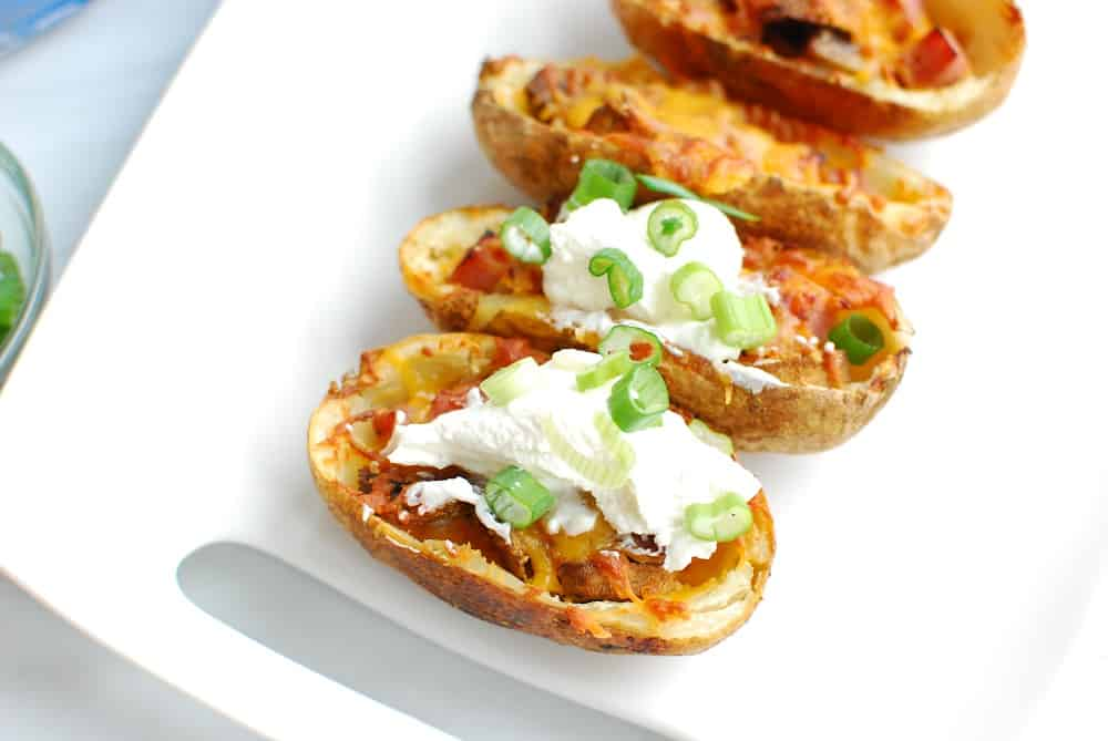 Air fryer potato skins on a platter, some of which are topped with sour cream and green onions