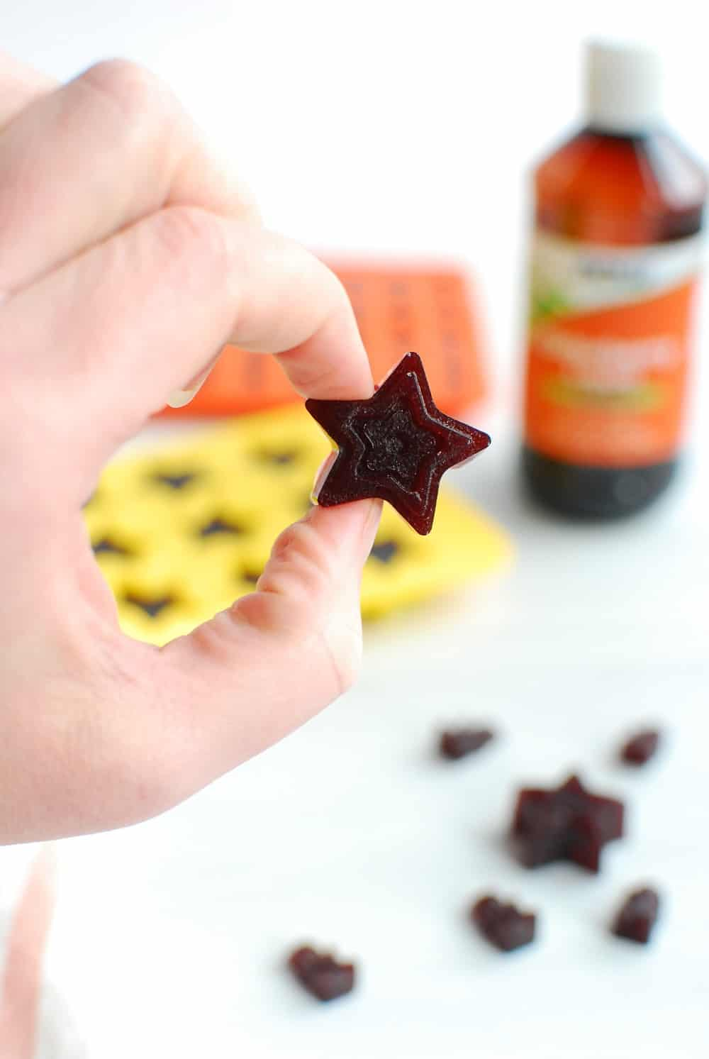 a woman holding a star shaped elderberry gummy