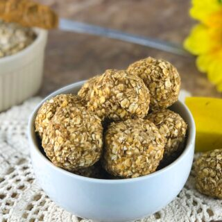 a bowl full of peanut butter banana oat balls on a wooden table