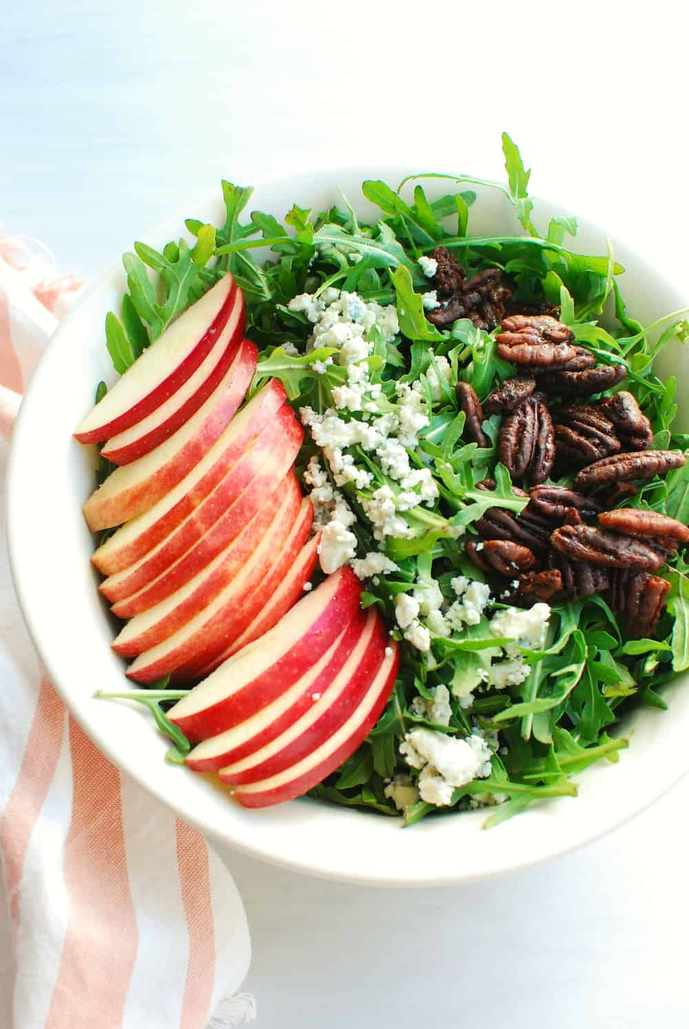 A bowl filled with arugula, apples, blue cheese, and pecans