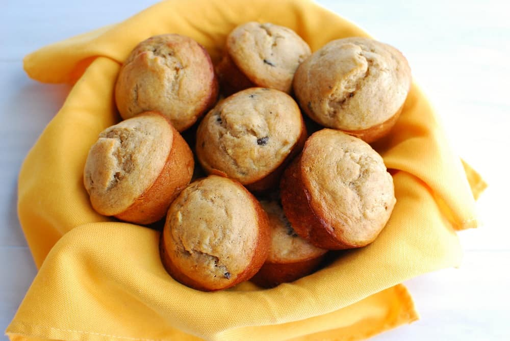 a bowl lined with a yellow napkin filled with a bunch of healthy banana muffins