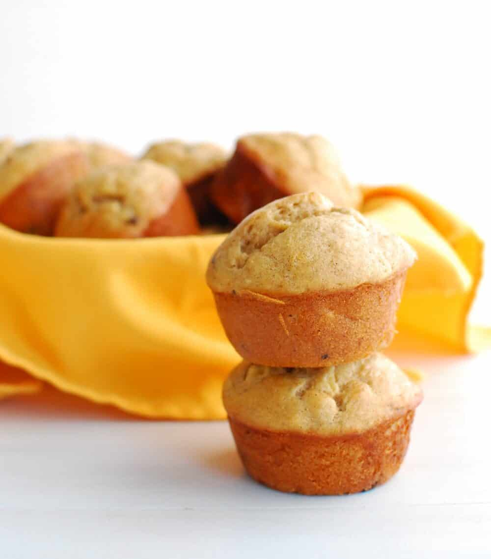 two banana muffins stacked up next to a bowl full of muffins