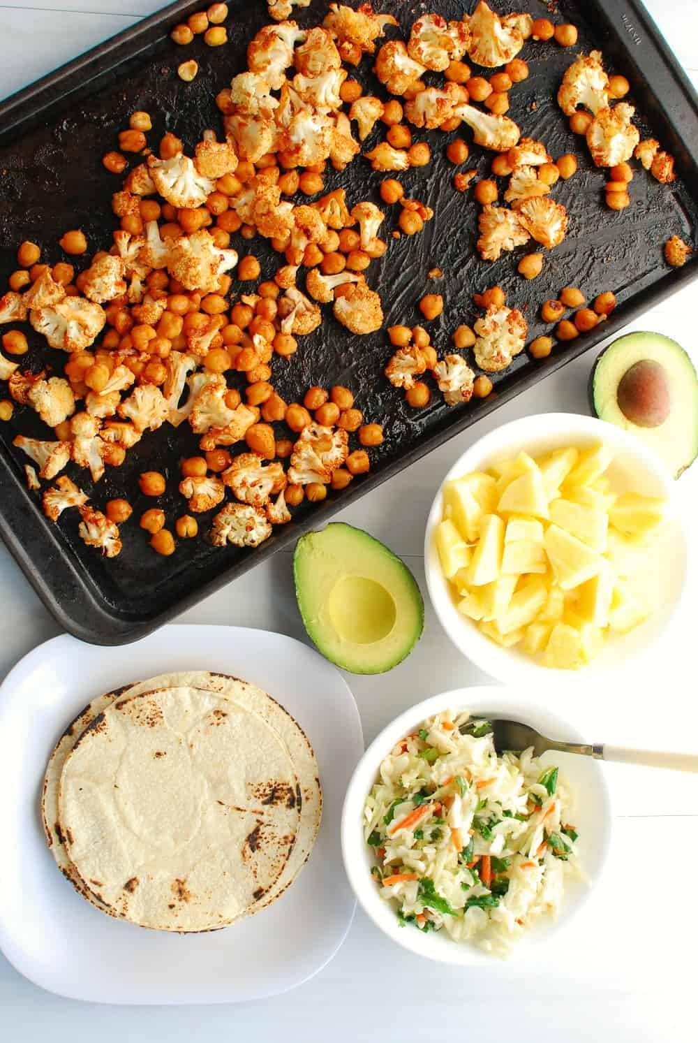 a pan of bbq cauliflower and chickpeas next to a plate with corn tortillas, a bowl with pineapple, an avocado, and a bowl of cabbage slaw