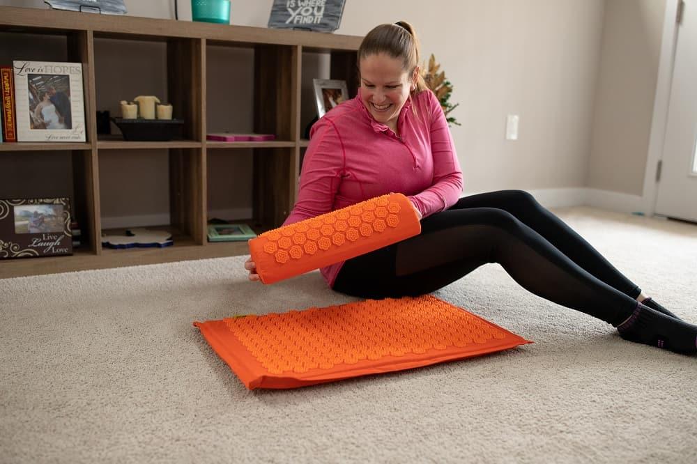 A woman holding an acupressure mat