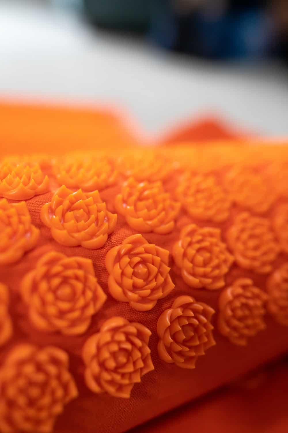 an acupressure pillow with hard plastic flowers