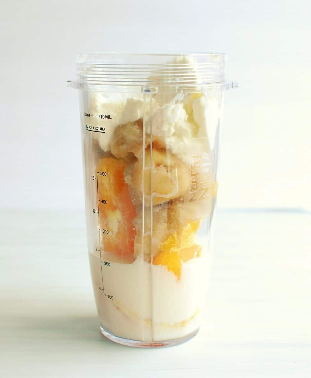 a blender cup full of banana, orange, yogurt, and milk