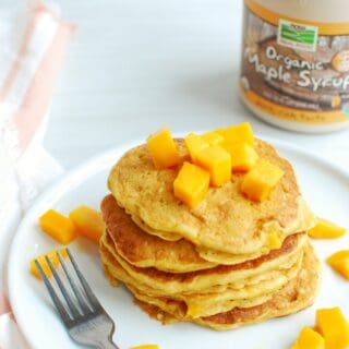 a stack of mango pancakes on a white plate, topped with extra mango