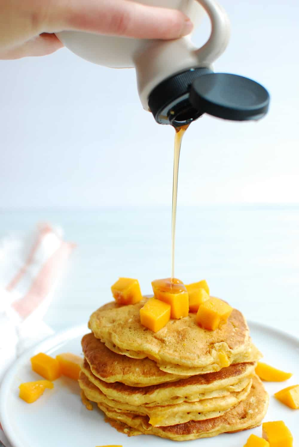 a woman pouring maple syrup onto a stack of pancakes