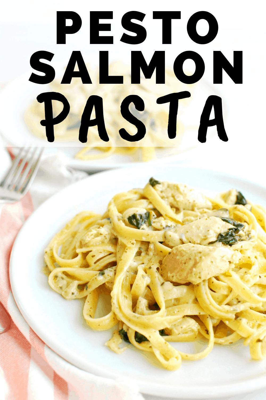 a plate full of pesto salmon pasta next to a striped napkin